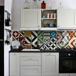 Colorful backsplash with random patterns black countertop white kitchen cabinets two kits for hanging cooking tools