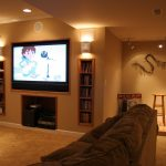 Combined lighting fixtures for basement with comfy sofa brown wool rug built-in book shelves built in media storage