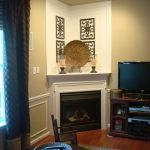 Corner fireplace mantel with a pair of classic candle stands several wall niches Turkish rug for wood floors a TV cabinet with flat TV  a rounded wood table a small wood chair full length window curtain