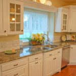 Country kitchen backsplash idea with luxurious marble kitchen counter double sinks and faucet white kitchen cabinets underneath and at the top