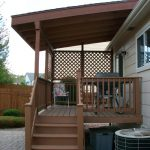 Cover idea for small home deck  with vertical wood rails and outdoor stairway a patio chair