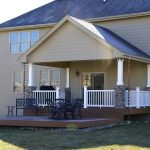 Covered home deck idea with black stained metal furniture vertical deck rails in white