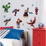 Creative and cool wall decoration with a lot of superhero stickers a red drawer system a bed furniture with multicolor pillows