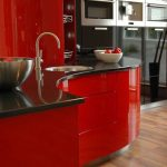 Curved kitchen island idea in bright red color and glossy black counter a rounded sink and stainless steel faucet bamboo floors system