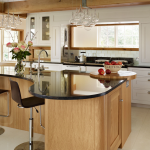 Curved kitchen island made from wood with black glass surface sink and faucet two barstools two units of pendant lamps a kitchen set in white theme plus kitchen storage white ceramic floors