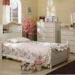 Darker brown bedroom rug idea a single classic bed furnitire with headboard a bedside table with drawer system a classic table lamp a classic vanity with storage and permanent mirror beautiful wallpaper