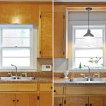 Double sinks and faucet a pendant lamp glass window with white trims granite kitchen counter wooden kitchen cabinetry