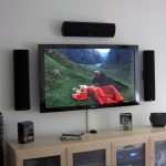 Floating TV set with audio systems surround it a wooden TV console with glass door shelving unit