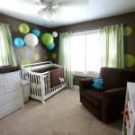 Fresh light blue and green curtains for a nurse room cute wallpaper some ball decorations on top ceiling lamp a single sofa for nurturing the baby a baby box in white baby clothes closet