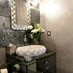 Glamour powder room with square decorative mirror with luxurious vanity light fixture textured wall system elegant black vanity with textured white sink and faucet