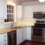 Glossy white subway ceramic tiles backsplash brown granite countertop with double sinks and faucet  a gas stove unit white kitchen cabinet idea a ceiling fan with lamp  a classic pendant lamp over the sink