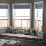 Half way corner window curtain or bay windows with corner bench under windows some throw pillows
