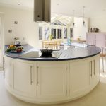 Kitchen island in curve shape with luxurious black counter electric stove a barstool a storage system in light purple