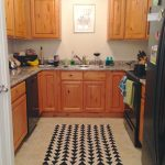 Kitchen rug with black triangle patterns U shape kitchen set with marble kitchen countertop original wood toned cabinetry
