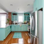 L shaped kitchen set with teal cabinetry and upper shelves with glass door white porcelain kitchen counter small kitchen rug gloss staining wood planks floors recessed light fixtures