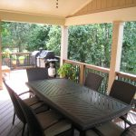Large home deck with cover railing system black theme rattan furniture and wood planks floor