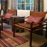 Layered rug ideas a pair of wood chairs white sofa and an Ottoman furniture