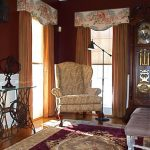Lighter brown curtains with upper decoration as the corner window curtain idea a comfy corner chair elegant and luxurious area rug with floral motif a classic free standing clock
