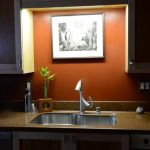 Lighting under cabinet a kitchen sink and unique shaped faucet an artistic painting with black frame wooden cabinets brown granite kitchen countertop