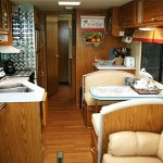 Lounge of RV with a pair of long chairs with table a small corner preparing table a small kitchen with storage sink and faucet with white ceramic countertop wood floors and cozy light brown leather sofa