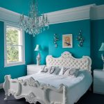 Luxurious bedroom design with turquoise wall paint color classic crystal pendant chandelier a classic bed furniture in white color a pair of minimalist bedside tables with table lamps a glass window