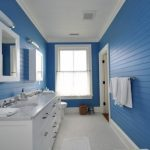Modern bathroom design for mobile homes with large vanity  a pair of floating cabinets with mirror door a glass window with half way white window curtain a permanent towel kit made from wood