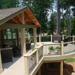 Modern covered deck for home with furniture and black vertical metal railing system
