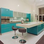 Modern minimalist kitchen design with teal base and upper teal cabinetry metal kitchen counter a minimalist kitchen island with white top a pair of barstools white ceramic tiles floors system