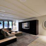 Modern minimalist living room idea with black L shape sofa wood top table grey skinny rug  minimalist black media storage oval framed decorative mirror