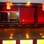 Modern pendant lamps in red color that are installed for basement bar