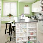 Modern style craft room for home office a standing crafting desk with open shelving systems two black stained wood chairs large and white painted storage systems for storing the works and crafting tools