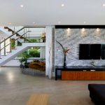 Mounted TV idea modern wood TV desk with glossy black surface and wooden structure a lot of recessed light fixtures a pair of decorative plants
