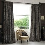 Patterned dark curtains in full length size a corner chair with two decorative pillows dark stained wood side table with table lamp