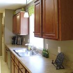Pendant lamp as the lighting for a kitchen sink light cream kitchen counter wood cabinetry