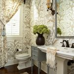 Powder room with square decorative mirror with silver frame a free standing sink and black metal faucet a grey painted console table with burned clay pot for plants beautiful floral wallpaper