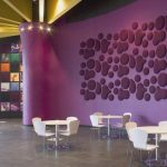Public seating with textured purple wall paint three sets of white conversation furniture