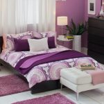 Purple wall paint for bedroom luxurious and comfy bed a white ottoman chair a black stained wood storage system a pair of round white bedside tables with wheels a pair of table lamps small pink wool rugs