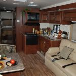 RV interior decoration with mini corner kitchen set a set of light cream sofa with grey pillows a set of dining furniture and hardwood flooring