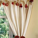 Red Christmas balls and red mini bells as window curtain ornaments