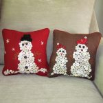 Red and brown throw pillows for sofa with creative Christmas ornaments made from buttons