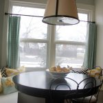 Round table in black staining some classic chairs a corner bench with throw pillows a large pendant lamp the glass window with window curtains