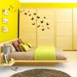 Simple And Bright Yellow Paint For Bedroom Wall With Unique Bedding And Yellow Blanket And Also Yellow And Brown Pillows Rounded Brown Wool Rug Built In Wood Bedside Table With Lamp