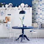 Simple but elegant kitchen set and dining furniture  in dark blue theme some dishware collections organized at permanent shelf and hung on the wall beautiful blue pendant lamp
