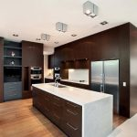 Simple modern kitchen design with white countertop and darker stained wood cabinets a kitchen island with pure white surface and darker painted wood storage modern light fixtures on ceiling wood floors
