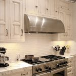 Simple white subway tiles for backsplash large and modern gas stove expensive white marble countertop white painted wood cabinets