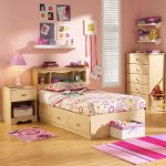 Small sweet bedroom rug with strip pattern a mat in purple and pink combination a wooden single bed with storage and headboard wooden bedside table with table lamp a drawer system made of wood