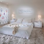 Smooth white wool bedroom rug in large size white bedding loft white bed furniture with white headboard a pair of white bedside tables with white table lamps large white bookshelves