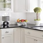 Subway tiles backsplash in white color black kitchen countertop with double sinks and faucet white porcelain decorative pot for bonsai a decorative plate for fruits s decorative table lamp white cabinets