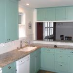 Teal kitchen cabinetry with metal handle granite kitchen countertop recessed light fixture over the kitchen sink a glass window with half way lace window curtain