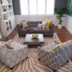 Three comfy sofas with different motifs plus pillows medium size rug with modern pattern hardwood floors white wooden rack for storing decorative items unique and beautiful pendant lamp